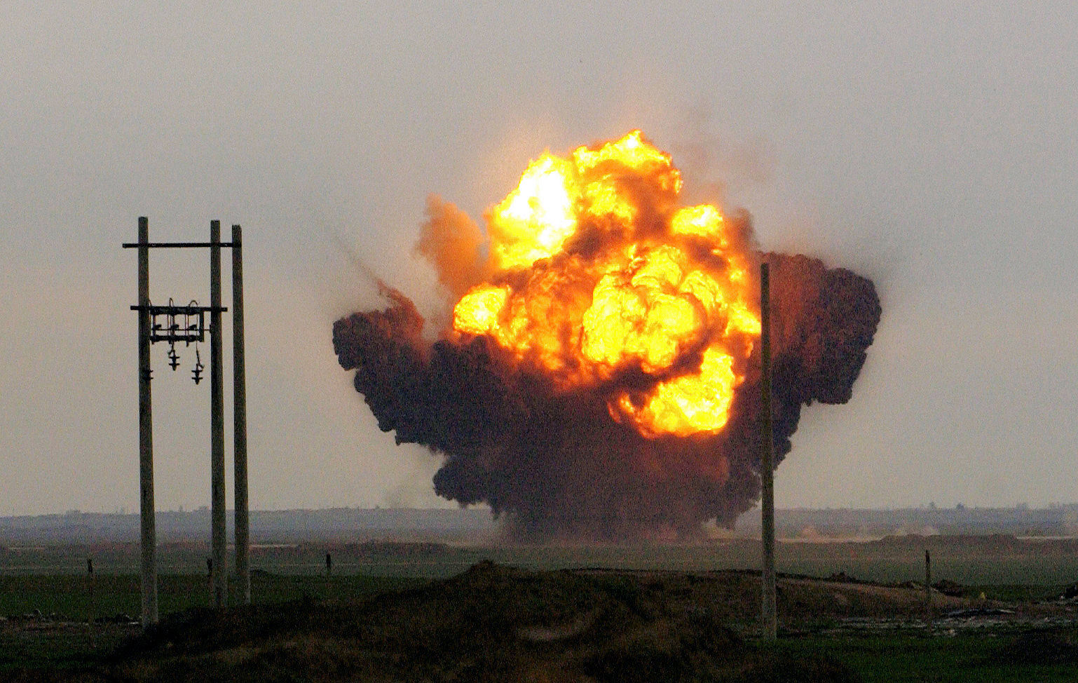 Explosions rock Al Fathah Air Field in Iraq, as Army engineers and Air Force EOD personnel work together to detonate a weapons cache.  An estimated two-million net pounds of explosives were left at the air field by the old regime, making Al Fathah the largest single weapons cache uncovered by the coalition, and they are destroying it at an average of 100,000 pounds per day.  (Photo by USAF Staff Sgt. Jeffrey A. Wolfe)  RELEASED